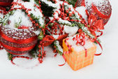 Christmas tree in the snow with red balls and gift box — Stock Photo