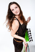 Young happy woman in dress with colorful shopping bags on a whit — Stock Photo