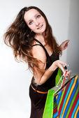 Jovem mulher feliz num vestido com sacolas coloridas em um whit — Foto Stock