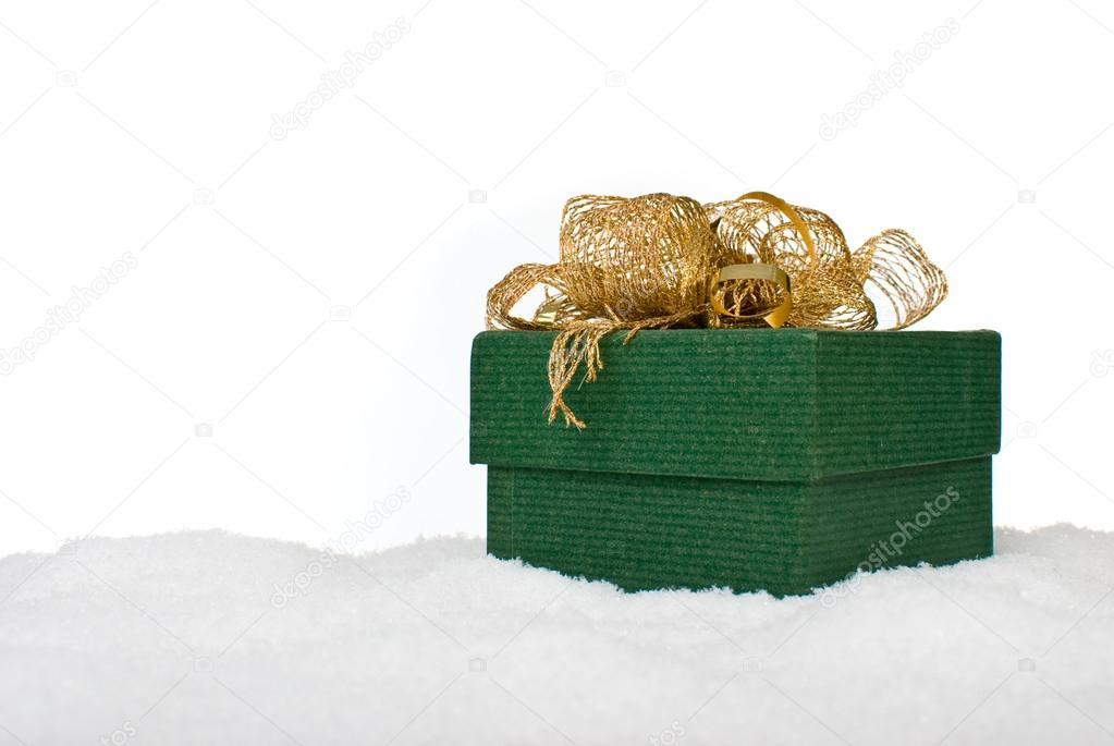 Christmas green gift box with gold ribbon in snow on a white background. — Zdjęcie stockowe #13490694