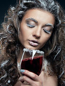 Portrait of young woman with snow make-up with a glass of wine. — Stock Photo