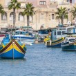Traditional Luzzu boat at Marsaxlokk harbor in Malta. - Stock Photo