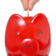 Stock Photo: Hand putting coin into the piggy bank