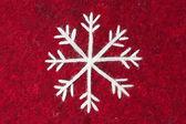 Roter Filz mit gesticktem weißen Schneeflocke — Stockfoto