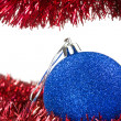 Christmas tinsel and blue bauble — Stock Photo