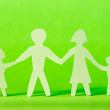 Paper family on green background — Stock Photo