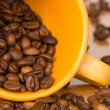 Yellow cup with many coffee beans — Stock Photo