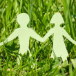 Paper family on a green grass — Stock Photo