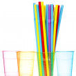 Plastic glasses and bunch of colorful straws — Stock Photo