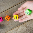 Hand throwing colorful dice  — Stock Photo
