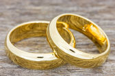 Wedding rings on a wooden floor — Stock Photo