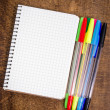 Stock Photo: Spiral notebook and colorful pens