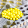 Spoon with yellow pills — Stockfoto