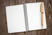 Spiral notebook and wooden pen — Stock Photo