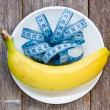 Banana and measurement tape in a plate — Stock Photo
