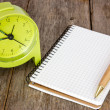 Stock Photo: Alarm clock and blank notebook
