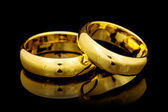 Golden rings on a black — Stock Photo