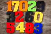 Plastic numbers on the wooden background — Stock Photo