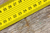 Yellow ruler on a wooden background — Stockfoto