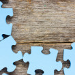 Puzzle on wooden boards — Stock Photo