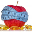 Apple and fish oil pills — Stock Photo