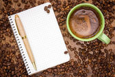 Notebook pen and cup of coffee — Stock fotografie