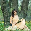 The girl is reading a book in the forest. — Stock Photo