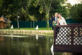 Bride and groom on the banks — Stock Photo