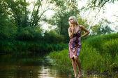 Muchacha rubia en un río del bosque — Foto de Stock