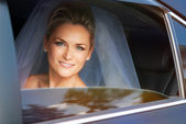 Beautiful young bride in the car — Stock Photo