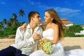 Happy newlyweds on a wild beach — Stockfoto