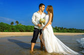 Happy newlyweds on a wild beach — Stock Photo