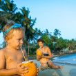 Small boy sitting on the beach and drinking coconut milk — Stock Photo #42154105