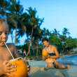 Small on the beach and drinking coconut milk — Stock Photo #42154175