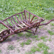 Wooden wheelbarrow on a green field — Stock Photo