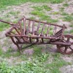 Wooden wheelbarrow on a green field — Stock Photo #26971749
