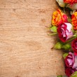 Multicolored roses on a wooden board - Stock Photo