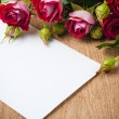 Bouquet of roses and white cardboard on a wooden board — Stock Photo