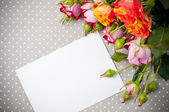 Roses and white cardboard on a gray fabric — Stock Photo