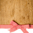 Wooden background with a red checkered ribbon — Stock Photo