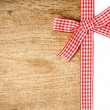 Stock Photo: Wooden background with red checkered ribbon