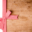Wooden background with a red checkered ribbon — Stock Photo #14087769