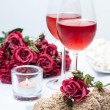 Two glasses of rose wine , fresh flowers, cakes — Stock Photo