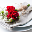 Table setting with red roses, napkins and vintage crockery — Stock Photo