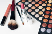 Colorful eyeshadows, lipstick and makeup brushes — Stock Photo