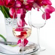 Glass of white wine and a festive table setting - Stock Photo