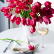 Home table setting with bright pink tulips - Stock Photo