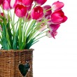 Bright pink tulips in a wicker basket - Stock Photo