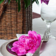 Table setting with pink peonies, vintage cutlery and brown table - Stock Photo