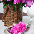 Table setting with pink peonies, vintage cutlery and brown table — Stock Photo